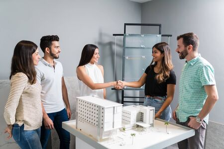 Hispanic business clients meeting shaking hands with architects in meeting at construction industry