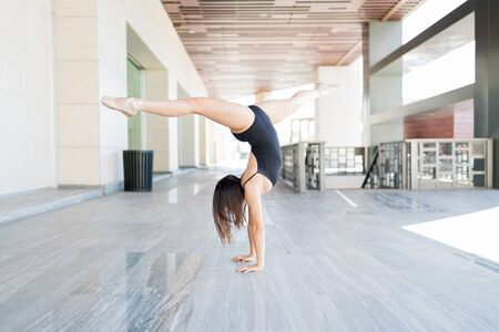 Talented young ballerina doing splits while balancing on hands in urban scene