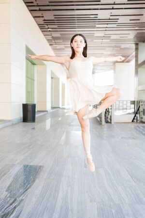 Female ballet dancer balancing on tip of her toe while dancing in the city