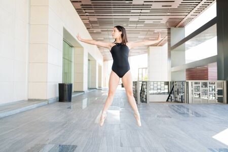 Female ballerina with arms outstretched tiptoeing while balancing on street in city