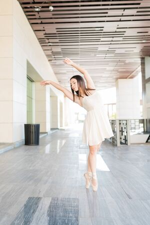 Good looking ballet dancer tiptoeing on pointe shoes while performing outdoors