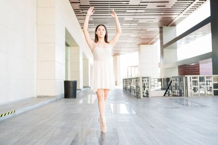 Confident attractive ballet dancer posing with arms raised on tiptoe at dance rehearsals