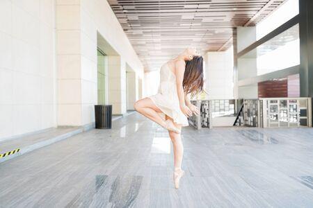 Charming female dancer tiptoeing while performing gracefully on urban scene Zdjęcie Seryjne
