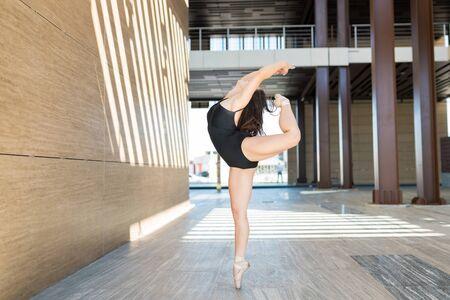 Brilliant ballerina bending backwards while balancing on one leg during dance routine