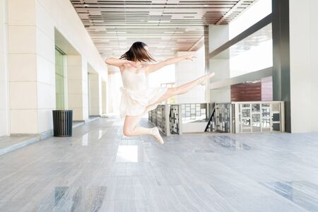 Young ballerina with tousled hair in midair enjoying dance on urban scene Zdjęcie Seryjne