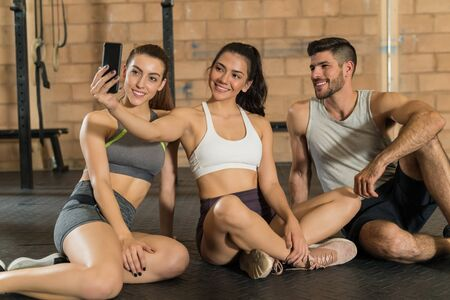 Smiling young female athlete taking selfie with friends while sitting at gym