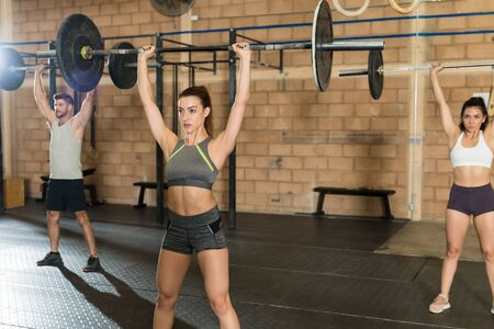 Confident Caucasian woman training with young athletes while weightlifting with barbells at gym