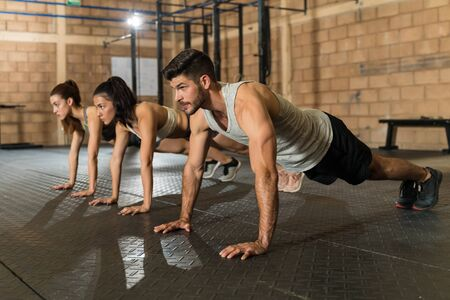 Confident young male and female athletes doing push-ups during cross training at gym