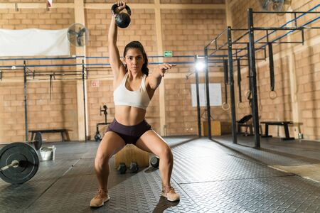 Dedicated young athletic woman exercising with kettlebell while doing squats at fitness club Zdjęcie Seryjne