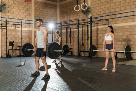 Young attractive male and female athletes lifting barbells during cross training at gym