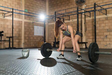 Pretty young female athlete preparing for weightlifting in cross training gym Zdjęcie Seryjne