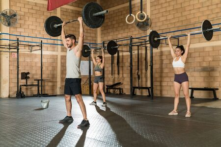 Active young athletic friends lifting barbells while working out at gym