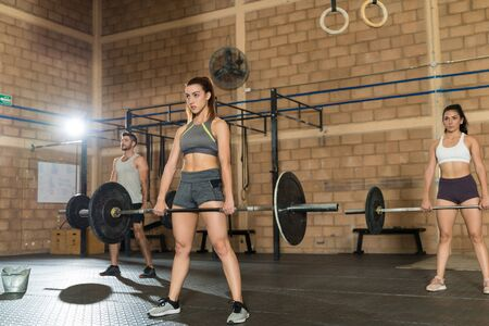 Gorgeous female athlete cross training with man and woman while lifting barbells at gym 版權商用圖片