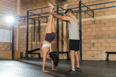 Full length of young man assisting friend in doing handstand at gym Zdjęcie Seryjne