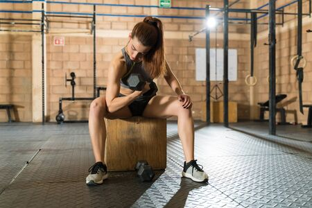 Caucasian young female athlete exercising while sitting on wooden box at fitness club 版權商用圖片