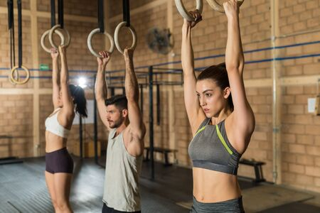 Young male and female athletic friends using gymnastic rings during cross training at gym Stok Fotoğraf