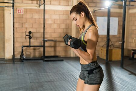 Side view of beautiful slim female athlete lifting dumbbells during cross training at gym