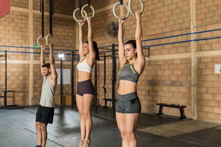 Confident male and female athletes hanging from gymnastic rings during cross training at gym