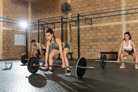 Confident beautiful Caucasian woman exercising with friends during cross training at gym