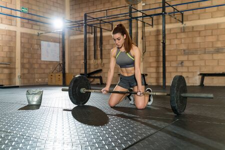Attractive sportswoman kneeling while contemplating and looking down before lifting barbell at health club