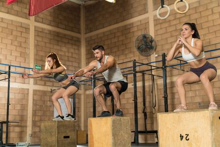 Young male and female athletes jumping onto wooden boxes during cross training in gym