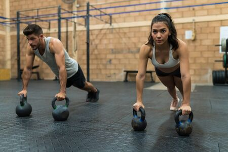 Sporty male and female athletes doing push-ups on kettlebells while looking straight in gym Zdjęcie Seryjne