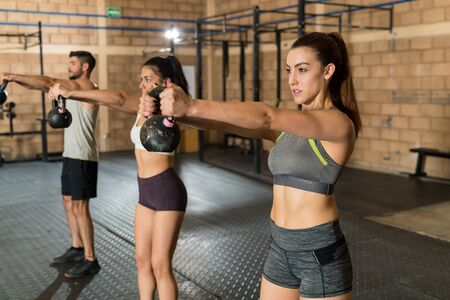 Gorgeous fit sportswoman exercising with kettlebell by athletes at cross training gym 版權商用圖片