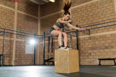 Beautiful young female athlete jumping onto a box during cross training in gym 版權商用圖片