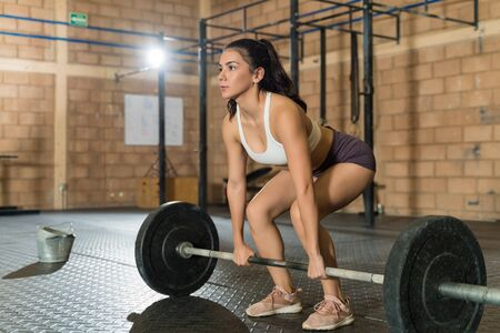Confident pretty female athlete looking straight while about to lift a barbell at fitness club