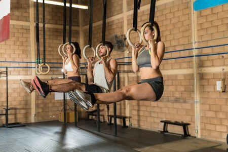 Full length female and male athletes pulling themselves up on gymnastic rings during cross training at gym