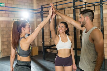 Happy young male and female athletic friends giving high-fives to each other while standing at gym