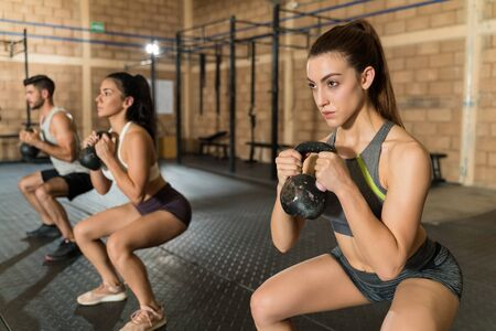 Confident beautiful Caucasian female athlete holding kettlebell while exercising with friends 版權商用圖片