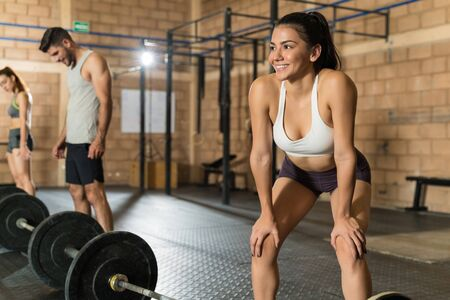 Smiling attractive sportswoman bending over after successful weightlifting session at gym