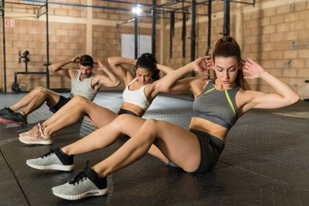 Beautiful young female athlete training with man and woman at fitness club Zdjęcie Seryjne