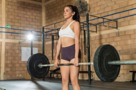 Gorgeous Caucasian sportswoman weightlifting while looking straight at gym during cross training