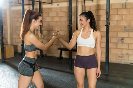 Smiling young attractive sportswomen shaking hands while standing at fitness club