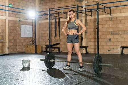 Portrait of gorgeous Caucasian athletic woman standing with hand on hip by barbell at health club 版權商用圖片