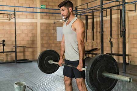 Confident Hispanic sportsman weightlifting while looking away at fitness club