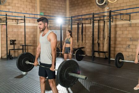 Latin man with young woman cross training with barbells at health club