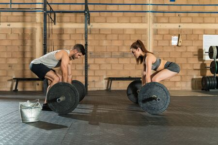 Young sporty female and male athletes lifting barbells at health club