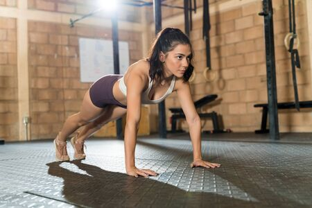 Full length of gorgeous young female athlete doing push-ups on floor at health club Zdjęcie Seryjne