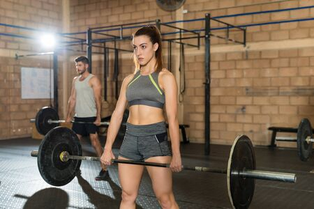Attractive sportswoman lifting barbell while training with sportsman at gym 版權商用圖片