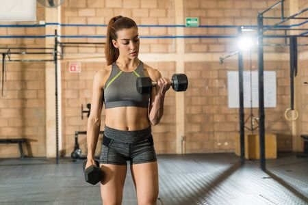 Gorgeous confident sportswoman exercising with dumbbells at health club