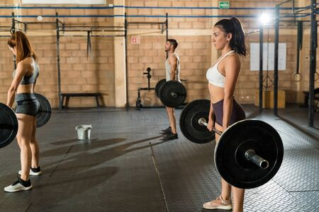 Side view of young female and male athletes holding barbells while standing in a cross training gym