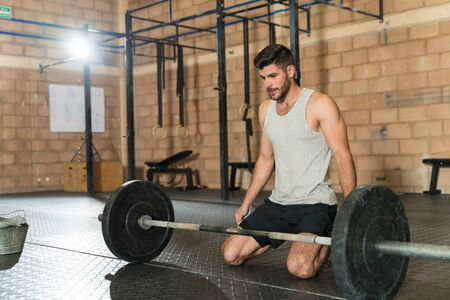 Handsome young male athlete kneeling and preparing himself mentally to lift the barbell at fitness club Zdjęcie Seryjne