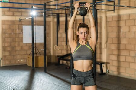 Confident slim sportswoman exercising while holding kettlebell over head at fitness club during cross training Zdjęcie Seryjne