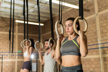 Gorgeous young sportswoman pulling her weight using gymnastic rings at health club