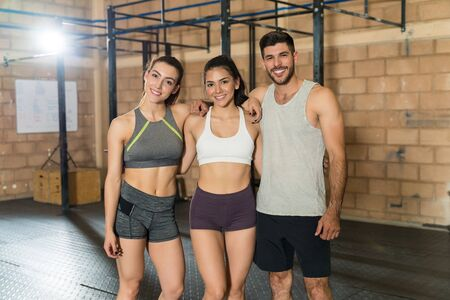 Portrait of smiling male and female friends standing with arms around at gym 版權商用圖片