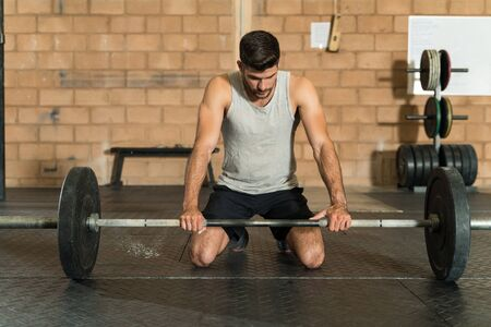Full length of sportsman holding barbell and contemplating while kneeling at gym