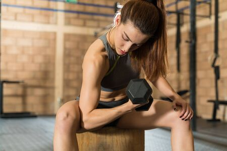 Dedicated athletic woman looking at her biceps while lifting dumbbell in a cross training gym 版權商用圖片